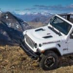 Jeep Wrangler top off driving off-road in front of mountains