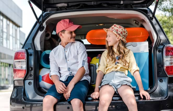 siblings sit in trunk of suv with beach gear