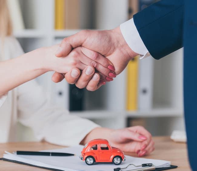 handshake over car signing