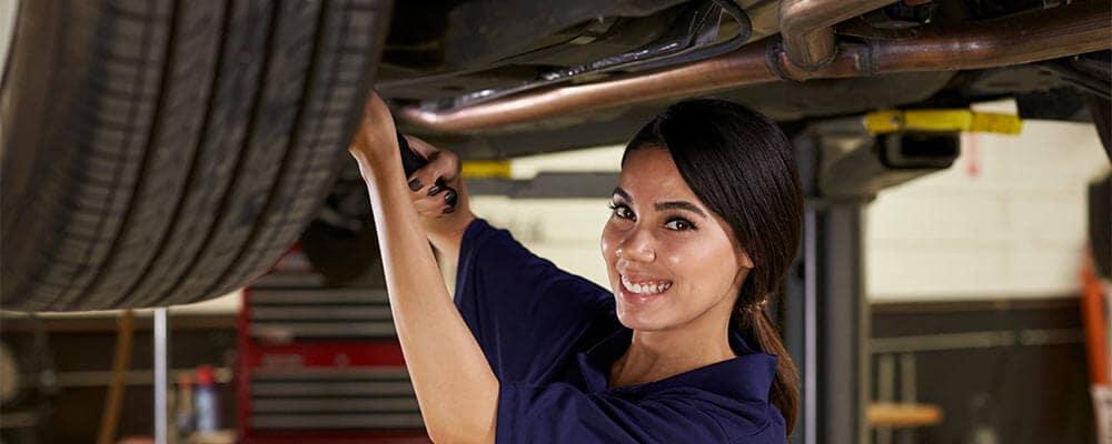 Female Mechanic Working Under Car