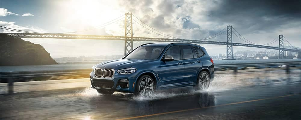 BMW X3 Driving Over a Bridge on Wet Road