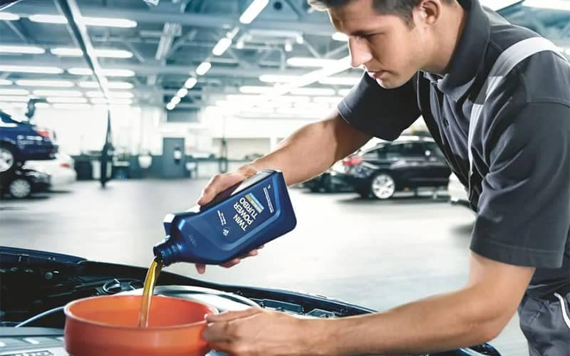 BMW Mechanic Pouring Oil Into Filter