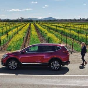 Exterior, left side view of the 2021 Honda CR-V Hybrid in red, in front of a backdrop of farmland.  Woman approaching car from the right side