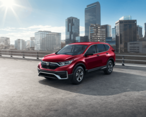Exterior view of a 2021 Honda CR-V in Red in front of a backdrop of city buildings