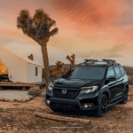 Front exterior view of the 2021 Honda Passport in black, surrounded by desert-located house and vegetation