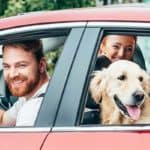 Happy family in car with dog