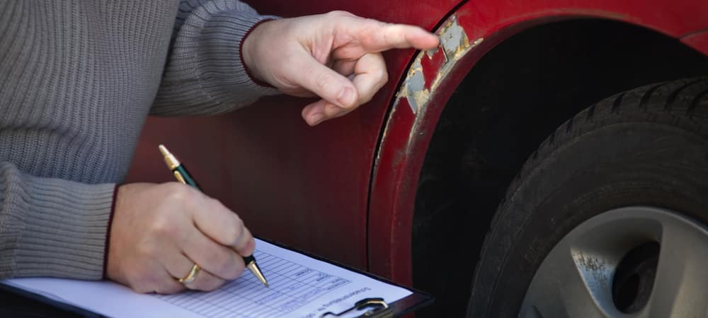 Claims adjuster taking notes next to a scratched car