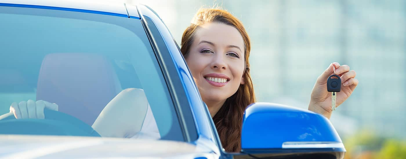 Woman holding keys out window of car she just bought