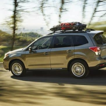 2018 Subaru Forester driving through a forest with cargo