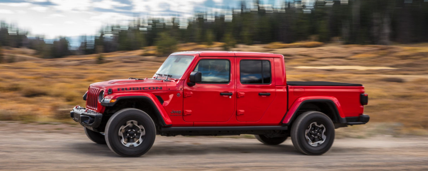Red Jeep Gladiator driving down the road