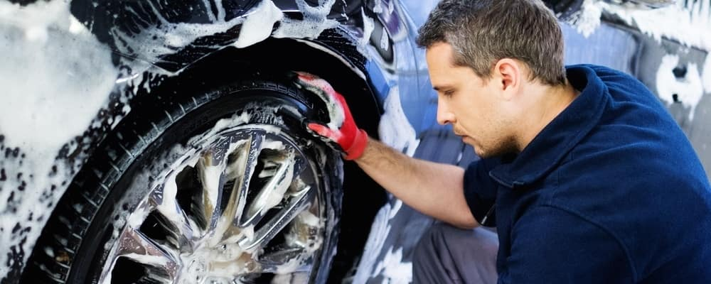 Man washing wheels of a car