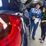 Mechanic explains the car repairs to the customer in his garage