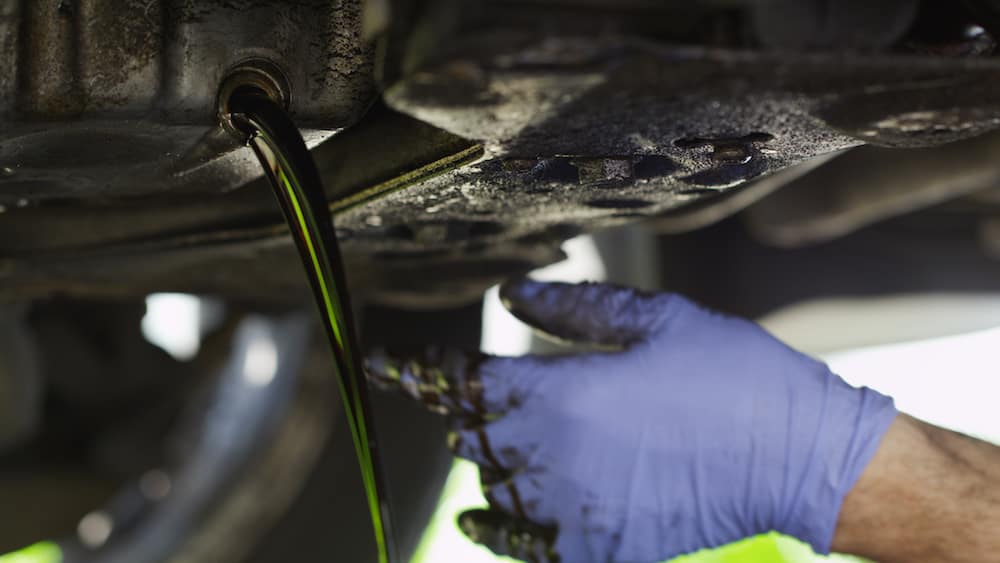 Blue gloved hand draining dirty oil from under car