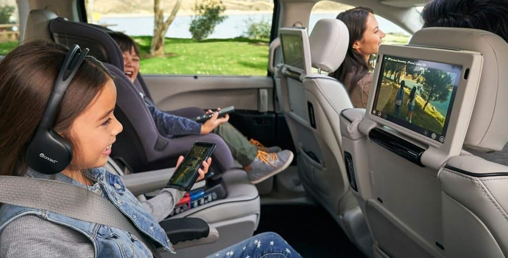 Two kids in the back seats of a 2020 Chrysler Pacifica enjoying the comfortable interior