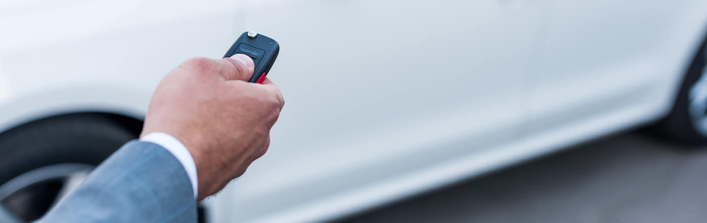 A man using a Dodge key fob to unlock his car