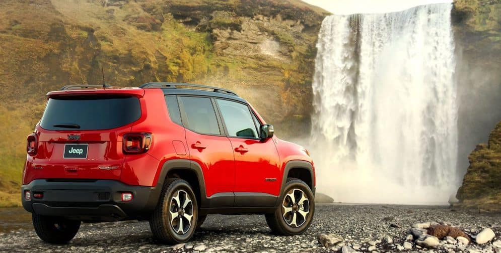 A red 2020 Jeep Renegade parked in front of a waterfall