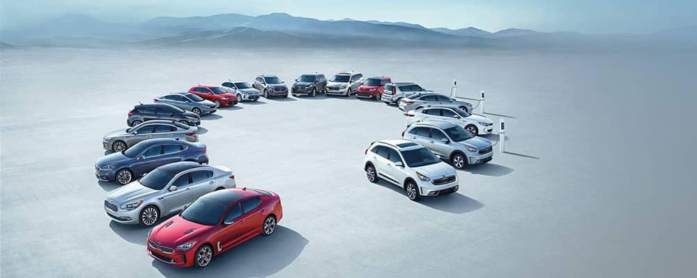 2018 Kia Model Lineup in a circle in front of Mountains
