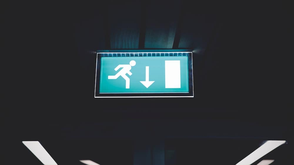 Exit sign with arrow pointed down and person running