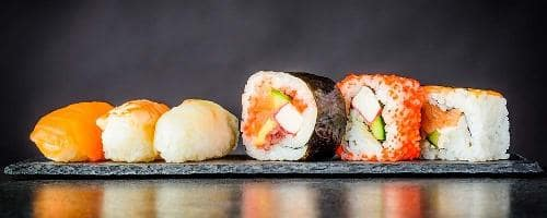 Row of sushi against black background and with reflection below