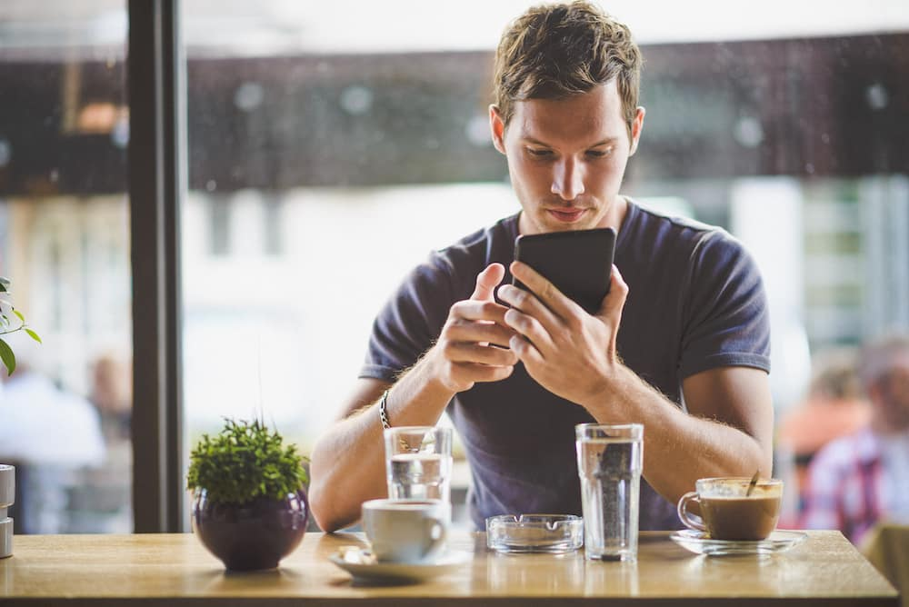 Man looks at tablet with espresso and water in coffee shop