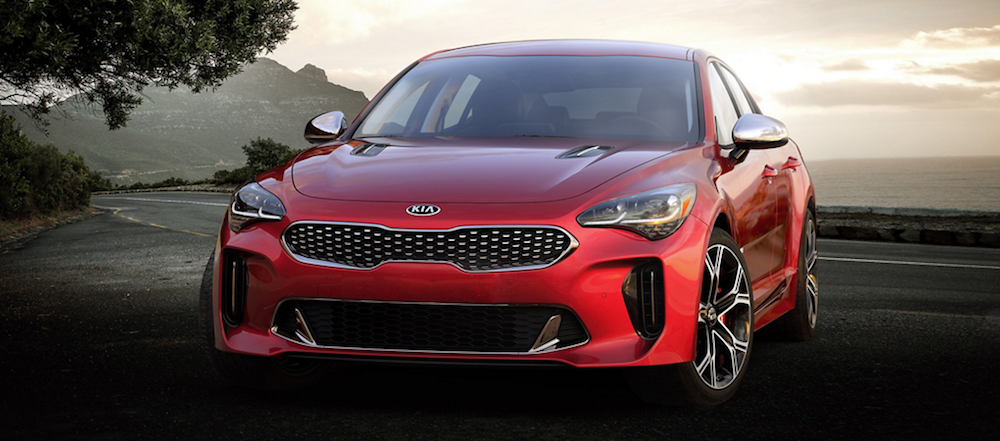 A red 2019 Kia Stinger parked in front of a lake