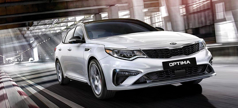 A 2020 Kia Optima driving on a city street