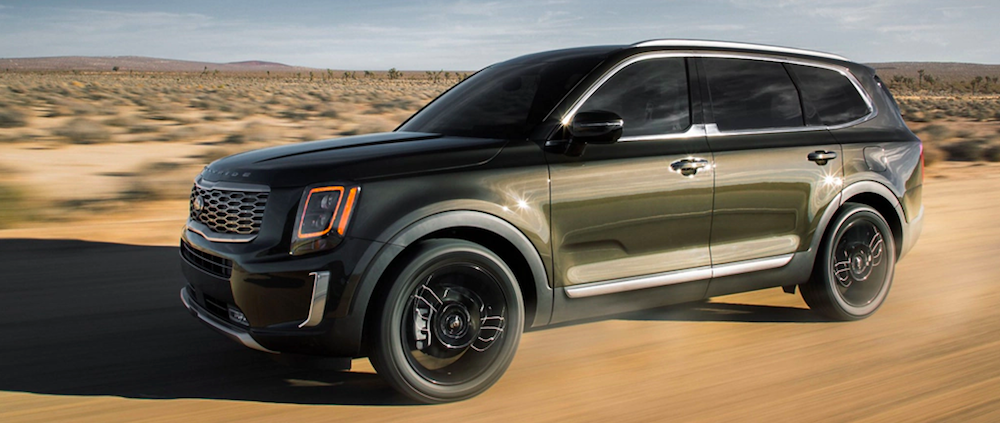 A 2020 Kia Telluride driving on a dirt road in the desert