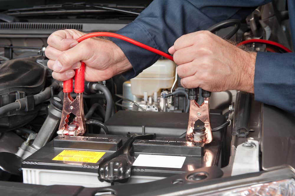 A car mechanic uses battery jumper cables to charge a dead battery