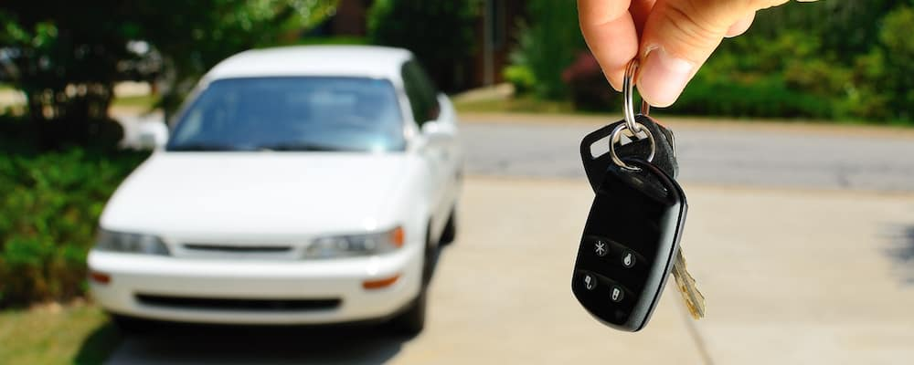 Handing over the keys to a white used sedan
