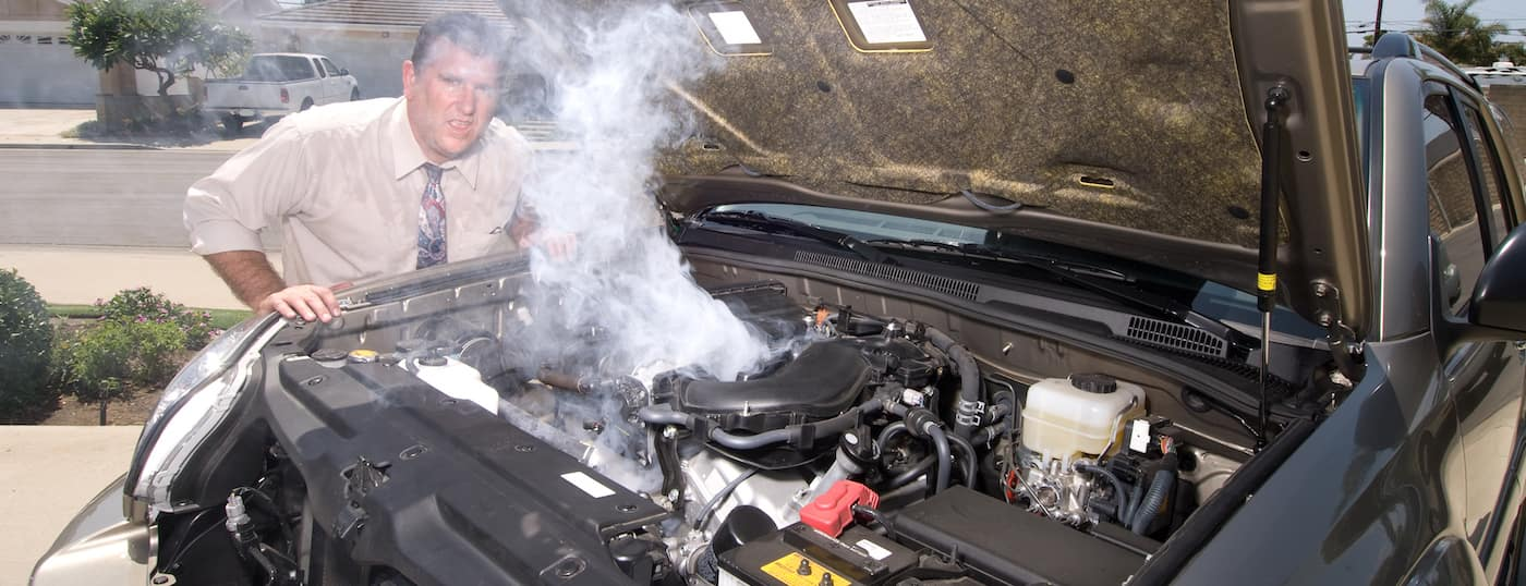 A frustrated man standing in front of an overheating car with the hood open