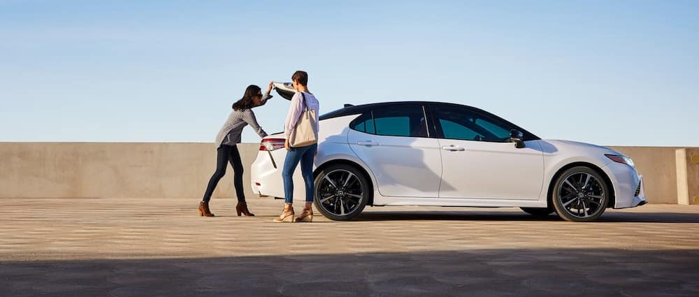 A young couple unloading the trunk of a used 2019 Toyota Camry