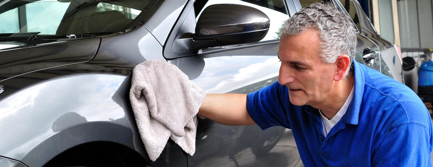 A man washing a car with a cotton rag