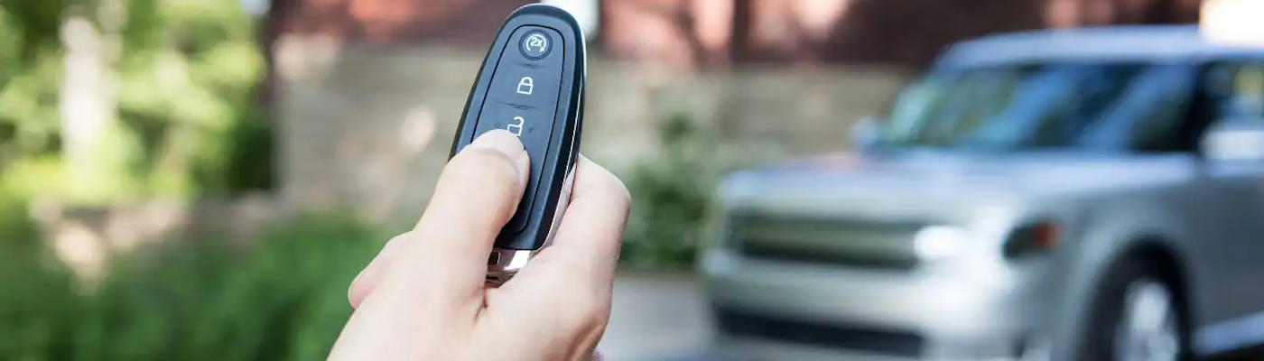 A person using their programmed Ford key fob to unlock their vehicle.