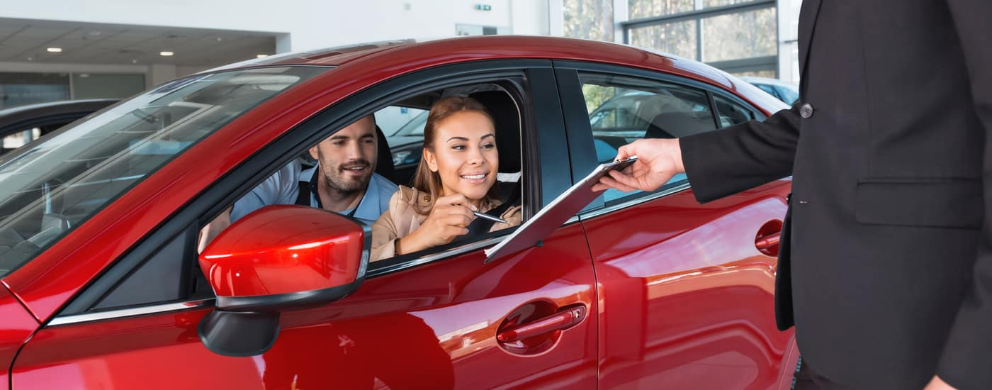 car buyers signing contract in car