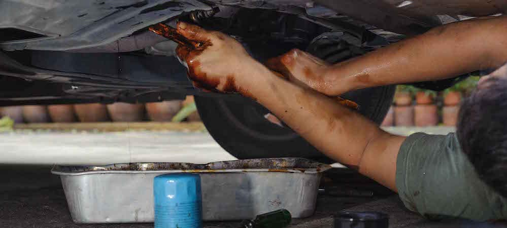 Car mechanic loosening oil filter