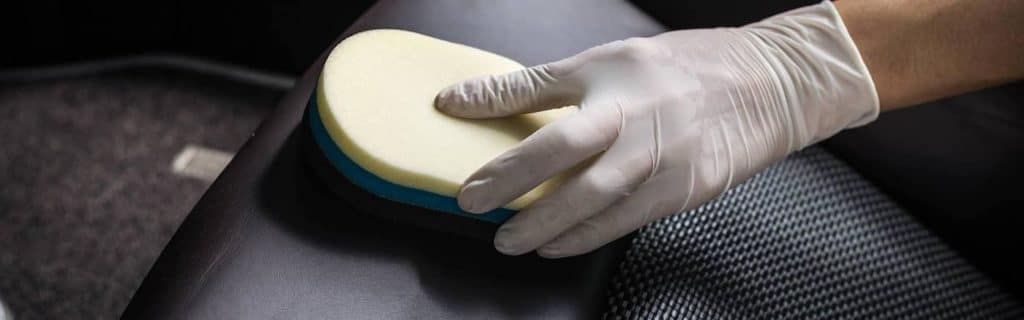 A person cleaning leather car seats with a sponge