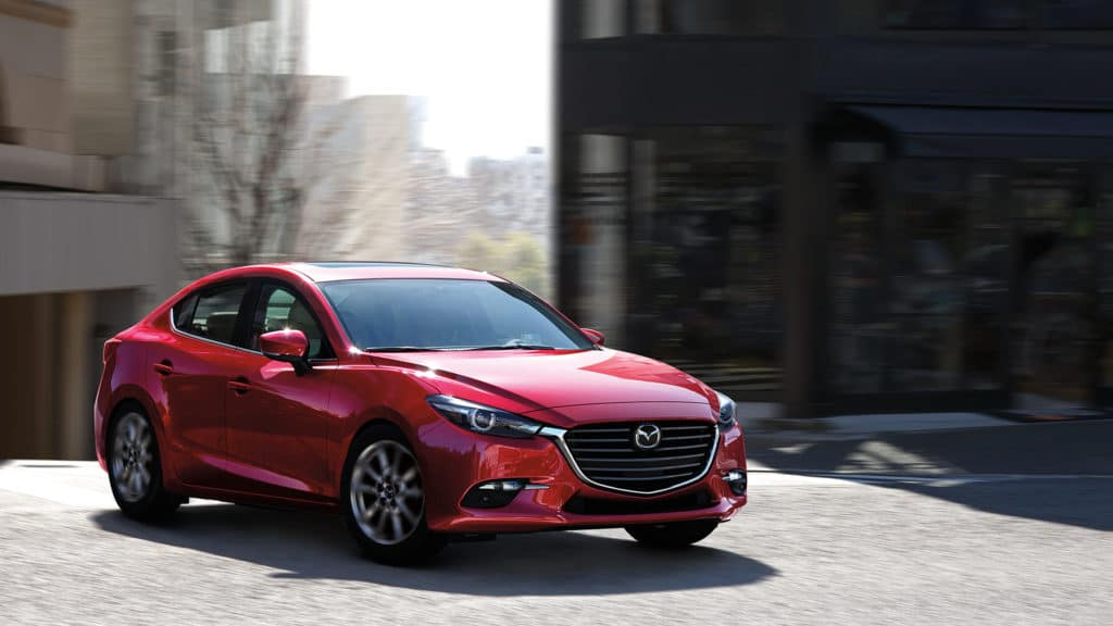 red 2018 mazda3 sedan driving in a city
