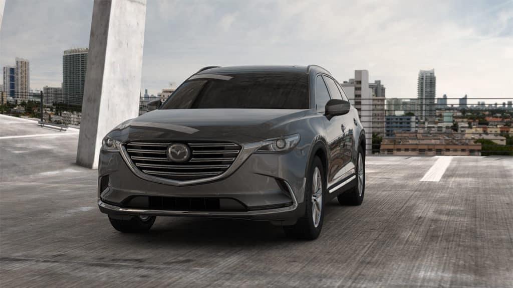 Grey Mazda CX-9 SUV against city skyline