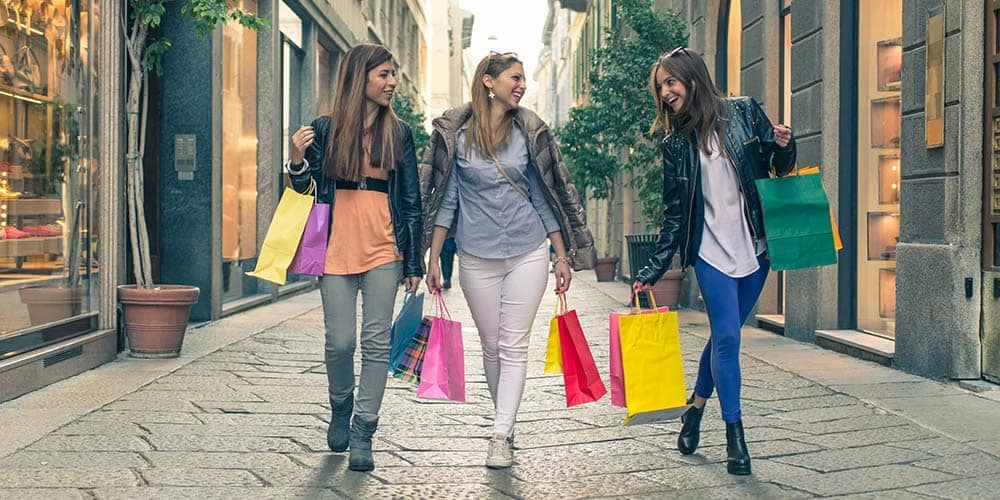3 Women Walking Down a Street of Shops holding Shopping Bags