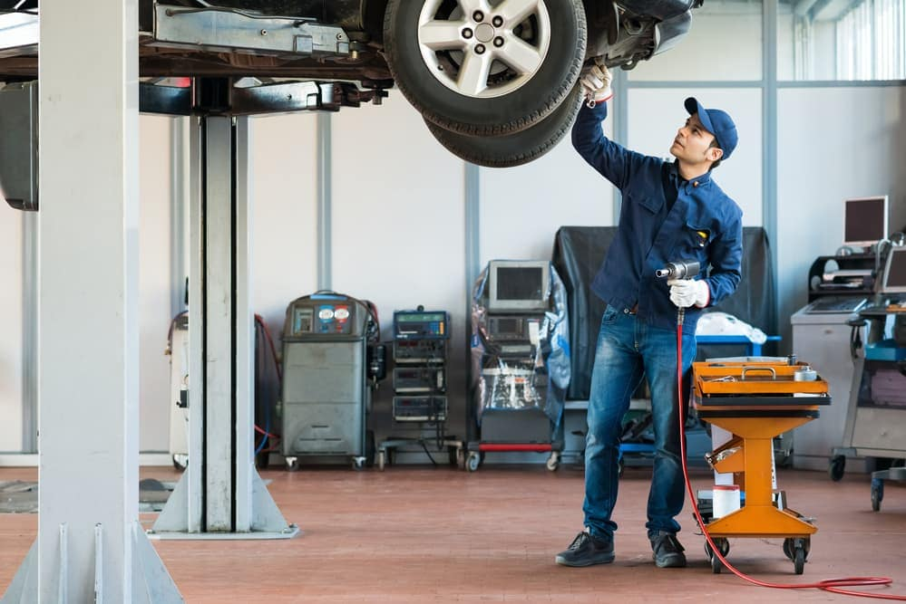 Auto mechanic with car on lift