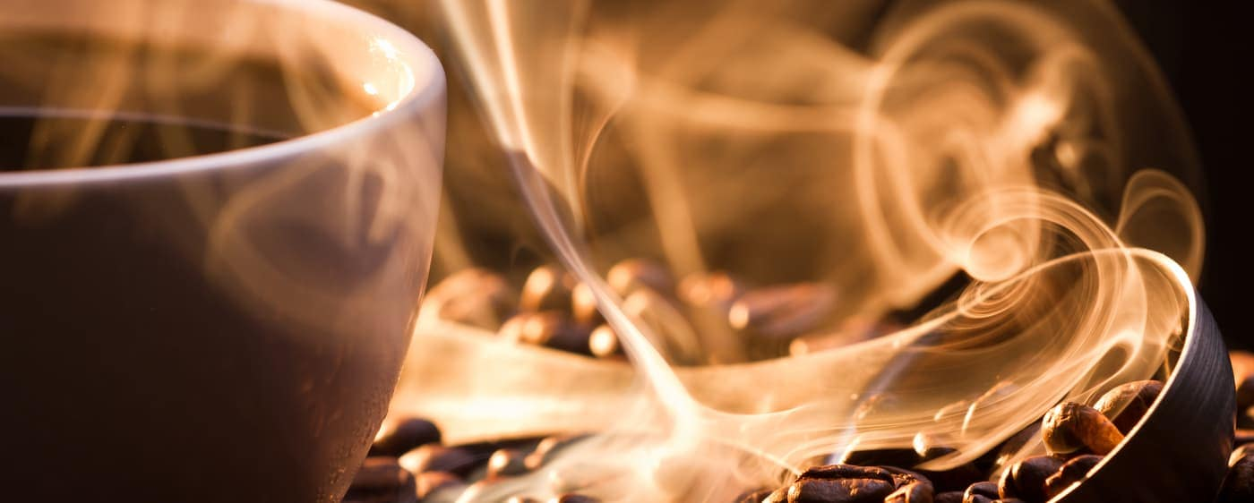 roasted coffee beans next to steaming coffee cup