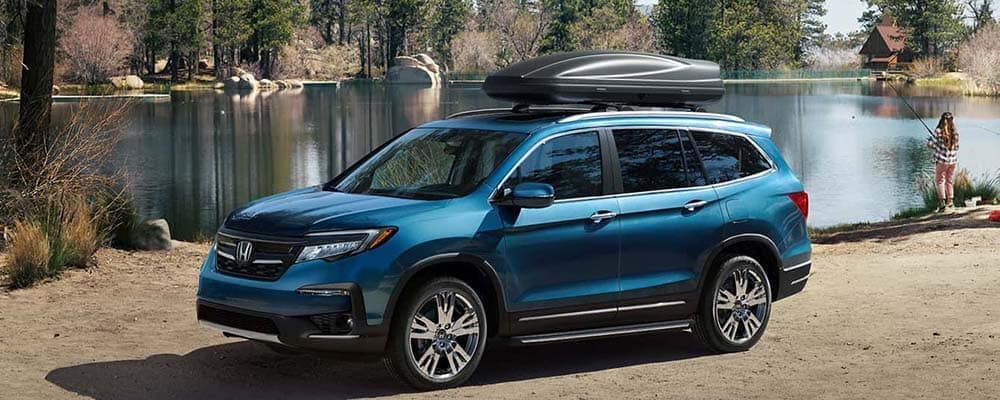 Blue Honda Pilot parked in front a lake with kayak on roof rack