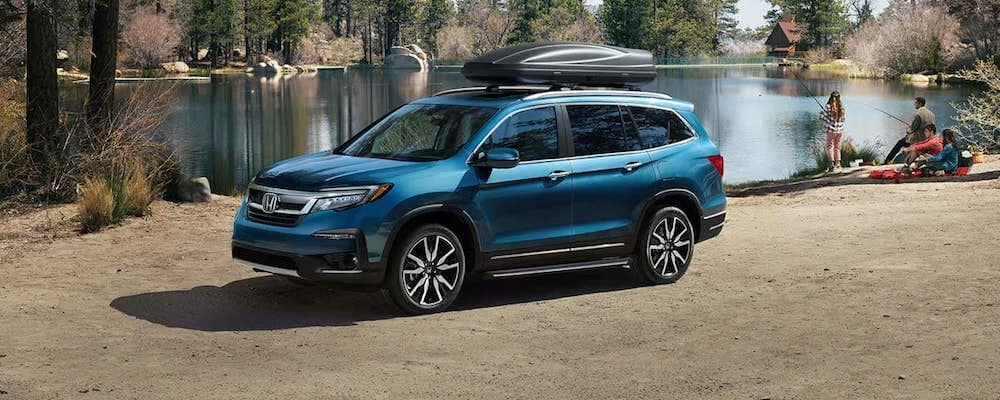 Blue Honda pilot with canoe on roof rack parked in front of a lake