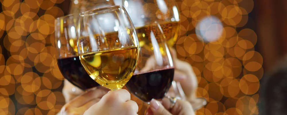 close up of people toasting with red and white wine glasses