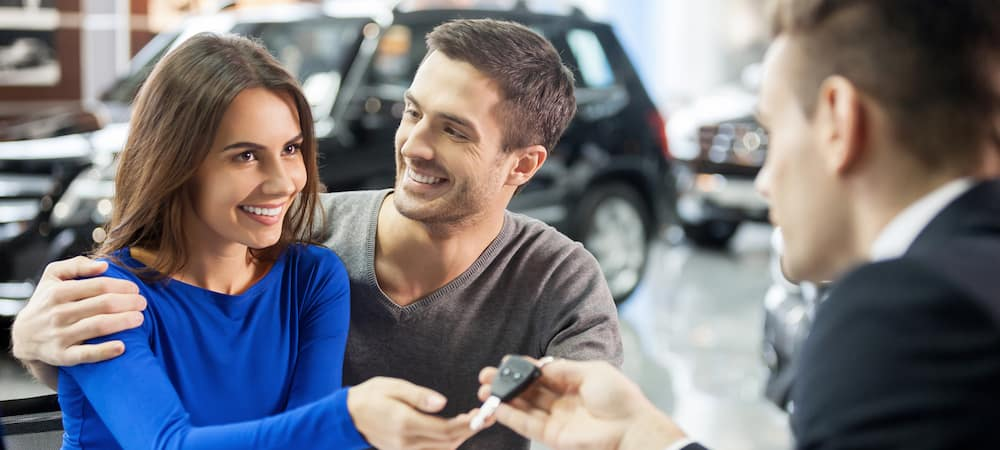 Salesman handing car keys to young man and woman