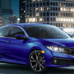 Blue Honda Civic Sport parked in front of tall buildings