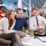 couple looking at laptop computer with salesman in new vehicle showroom