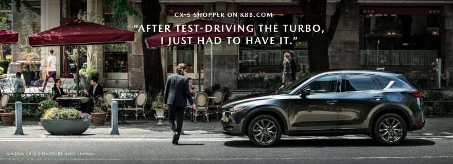 2021 mazda cx-5 on street in front of cafe with text overlay