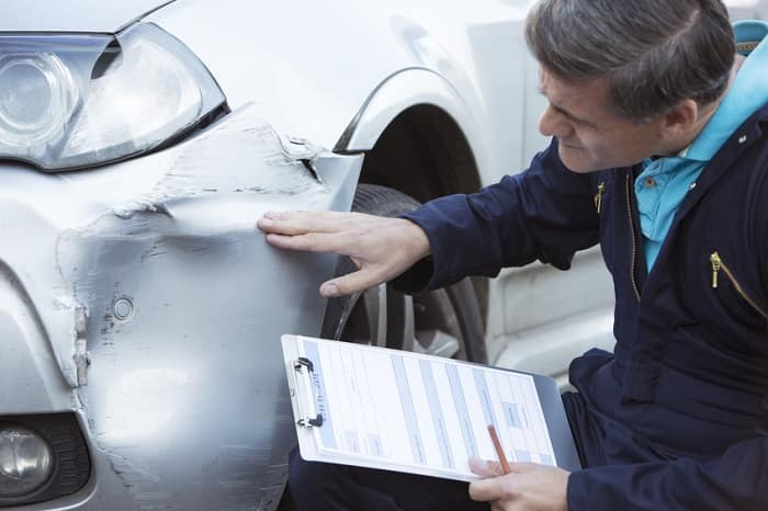 auto body shop technician inspecting car accident damage holding clipboard