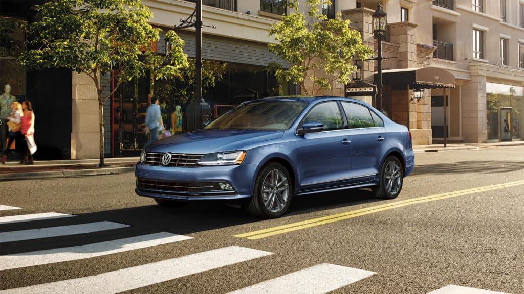 blue 2019 Volkswagen Jetta on a city street in front of shops